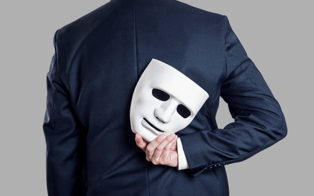 Business fraud concept. Businessman hide the mask in hand behind his back. stock photo