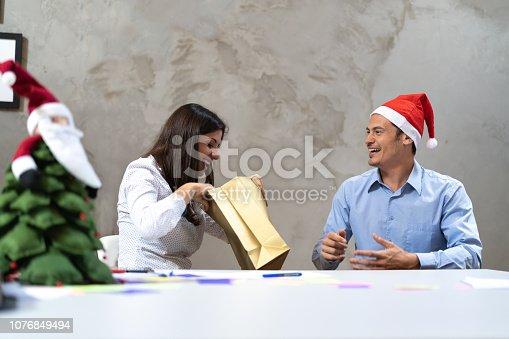 istock Business friends Exchanging Christmas presents at work / Amigo Secreto 1076849494