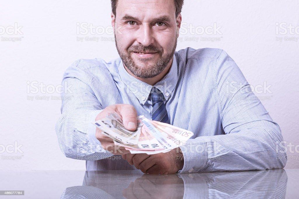 Business giving money towards camera stock photo