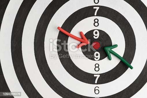Business goals or financial target, green and red arrow pointing at red dot center of black and white circle dartboard with score numbers.