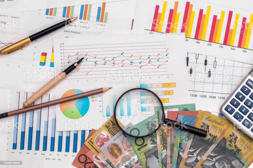 Business graphs with australian dollars, magnifier, pen and calculator stock photo