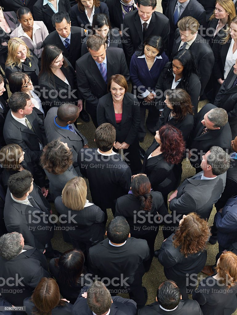 Business Group Looking At Woman In Middle stock photo