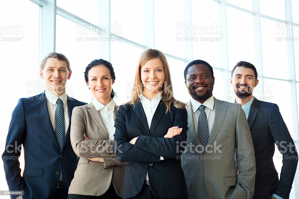Business group Group of business partners looking at camera with smiles, pretty leader in front Adult Stock Photo