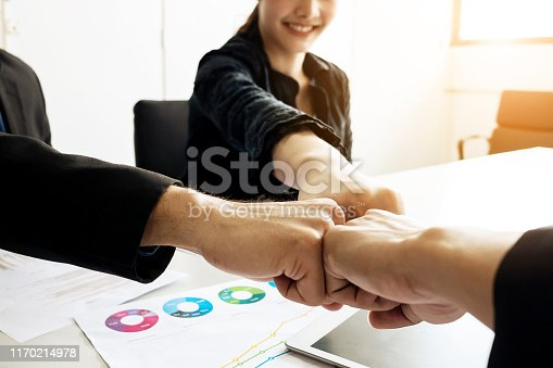 939533958istockphoto Business group team bumping hands up for teamwork project success. Combining power and encouragement 1170214978