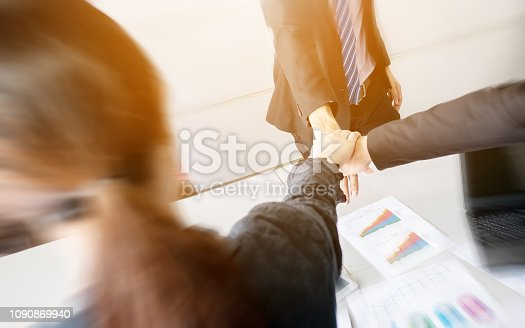 939533958istockphoto Business group team putting hands up for teamwork project success. Combining power and encouragement 1090869940