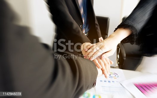 939533958istockphoto Business group team putting hands up for teamwork project success. Combining power and encouragement 1142945223