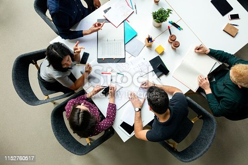 Top view shot of business colleagues discussing over a new project in office. Group of young men and woman brainstorming around table while working on new project.