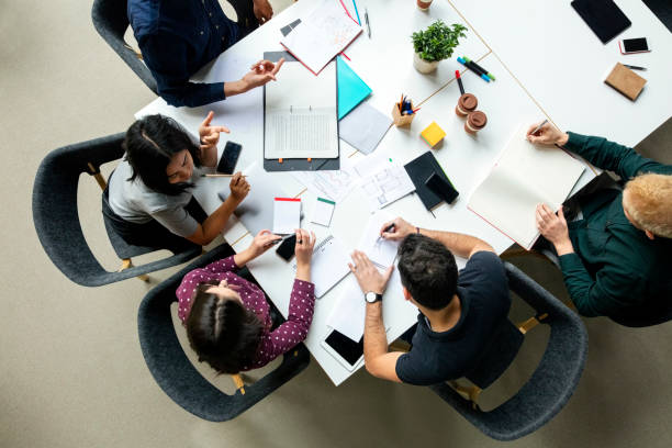 Business group working together on new project Top view shot of business colleagues discussing over a new project in office. Group of young men and woman brainstorming around table while working on new project. table top view stock pictures, royalty-free photos & images