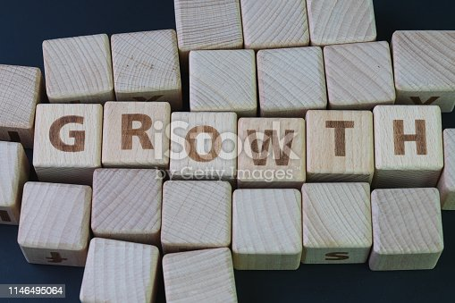 istock Business growth, company expand to get more revenue concept, cube wooden block with alphabet building the word Growth at the center on dark blackboard background, new opportunity in career path 1146495064
