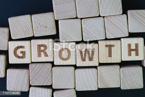 istock Business growth, company expand to get more revenue concept, cube wooden block with alphabet building the word Growth at the center on dark blackboard background, new opportunity in career path 1147226282