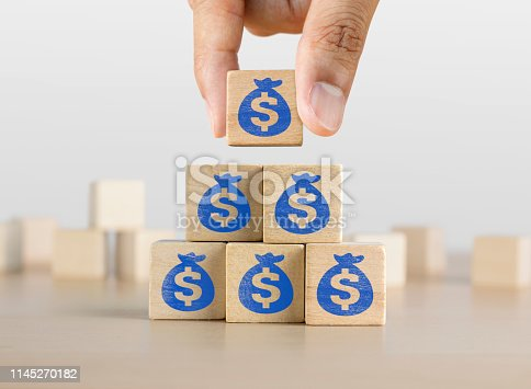 istock Business growth, increase profit, increase income or saving concept. Wooden blocks with the US Dollar symbol arranged in pyramid staircase and a man is holding the top one. 1145270182