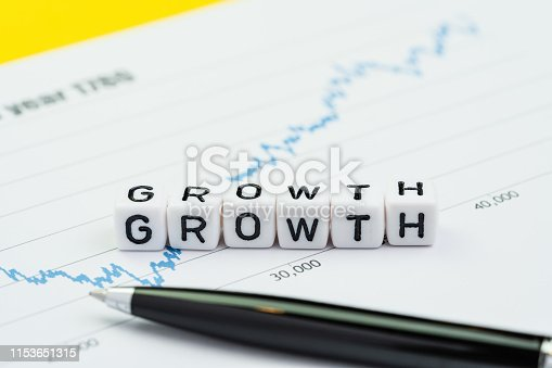 istock Business growth or return increase in investment concept, cube block building the word Growth on high positive chart and graph with pen 1153651315