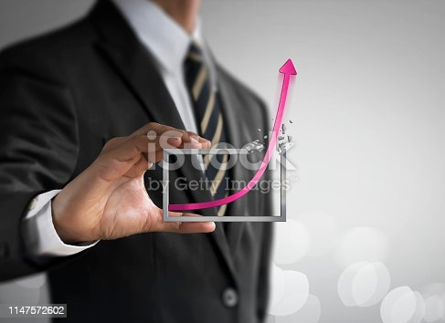 Business growth, progress or success concept. Businessman is holding a growing graph on bright tone background.
