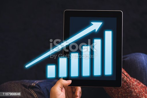 Hands holding digital tablet computer with business growth, success or development concept. Growing virtual hologram graph on dark. Top view