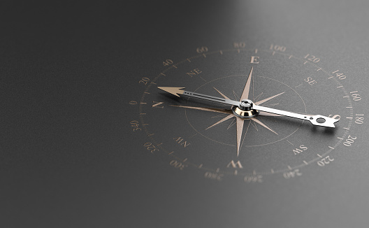 Golden compass over modern black background. Concept of business guidance or orientation, 3D illustration.