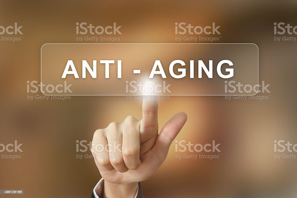 business hand clicking anti aging button on blurred background stock photo
