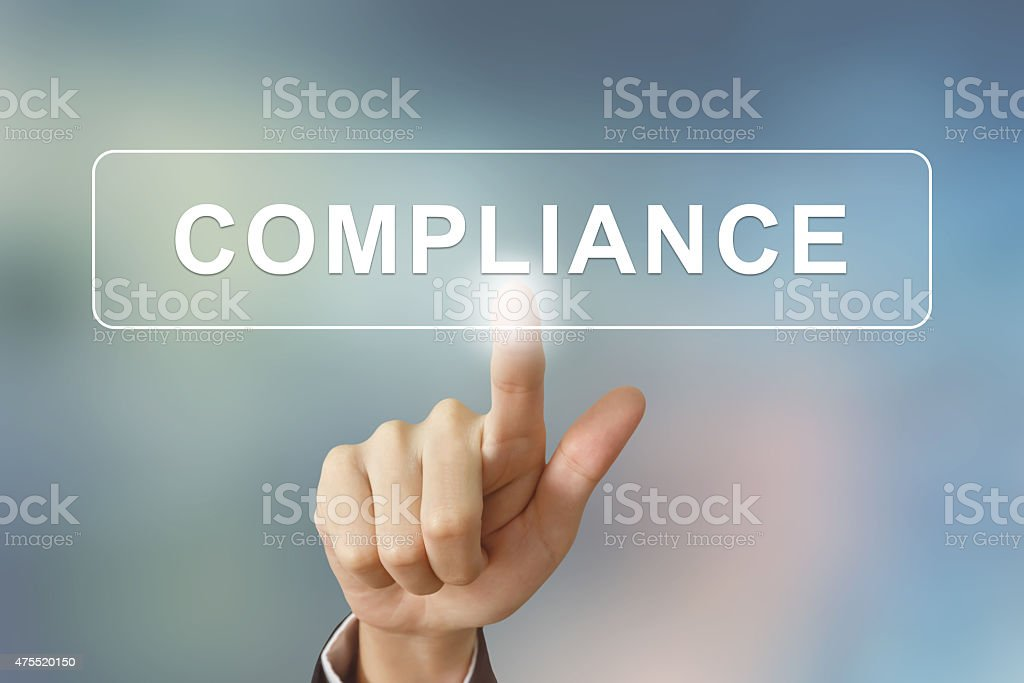 business hand clicking compliance button on blurred background stock photo