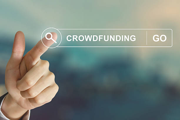 business hand clicking crowdfunding button on search toolbar stock photo