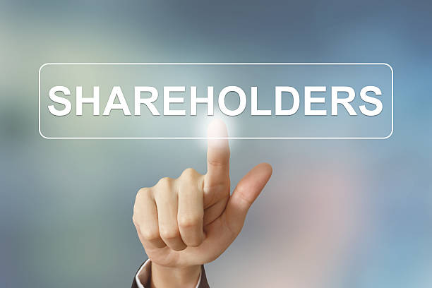business hand clicking shareholders button on blurred background stock photo