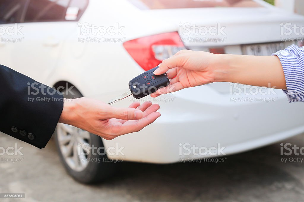 Business hand giving a key for buyer or rental car. stock photo