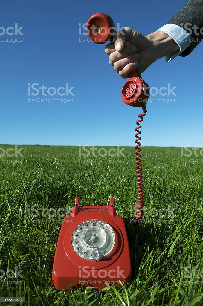 Business Hand Holds Red Phone Outdoors Bright Green Meadow royalty-free stock photo