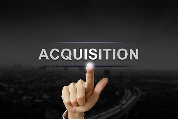 business hand pushing acquisition button stock photo