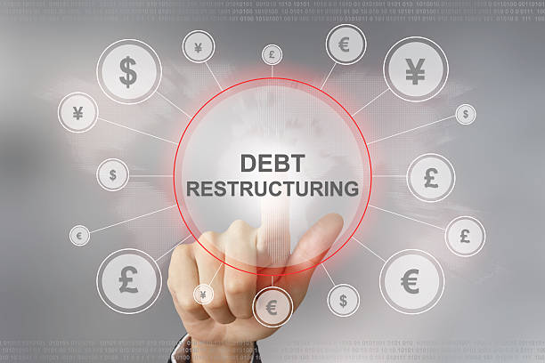 business hand pushing debt restructuring button stock photo