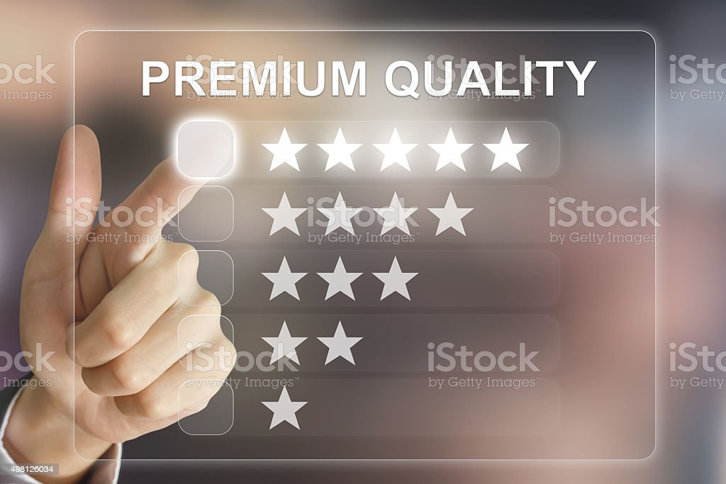 business hand pushing premium quality on virtual screen stock photo