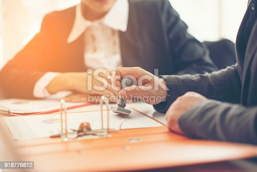 istock Business hand putting stamp on a document, close up 918776612