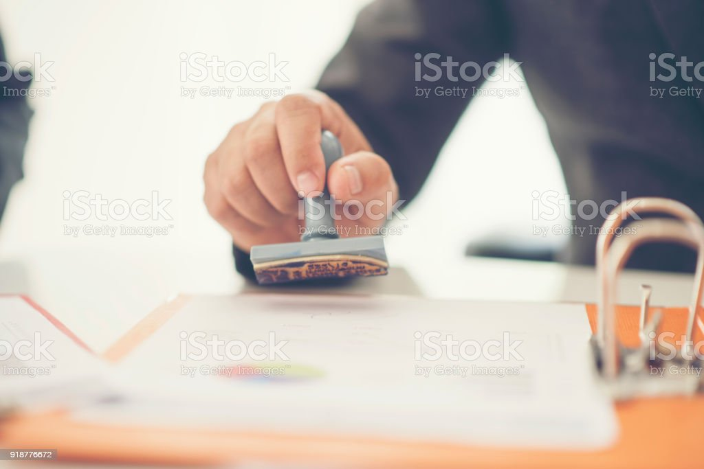 Business hand putting stamp on a document, close up stock photo