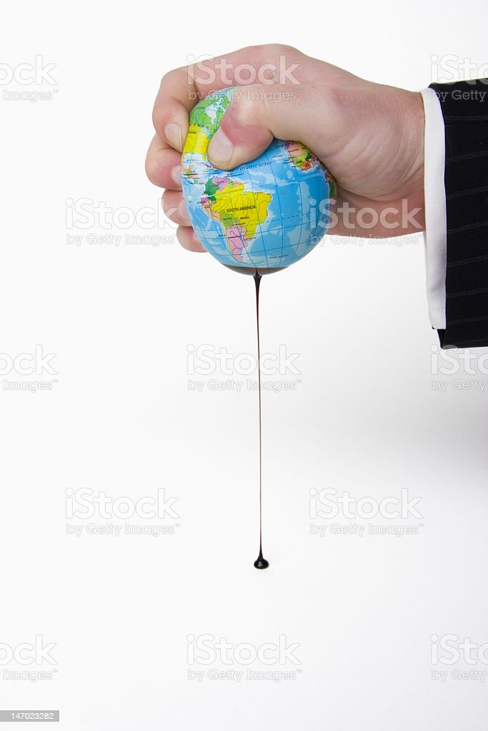 Business Hand Squeezing Long Drip of Oil from a Globe royalty-free stock photo