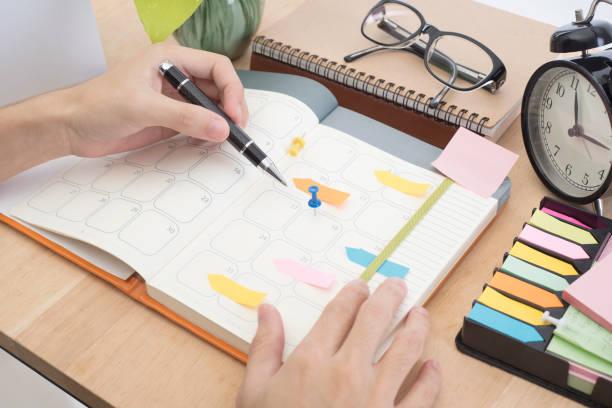 Unternehmen der Hand schreiben Kalender Planer am Schreibtisch Büro. – Foto