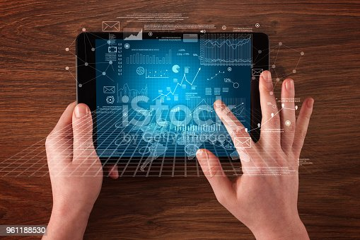 613550610istockphoto Business hands holding tablet 961188530