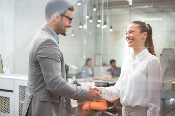 Business Handshake - Geschäftsleute schütteln Hände. Handshake zwischen Geschäftsmann und Frau drinnen. – Foto