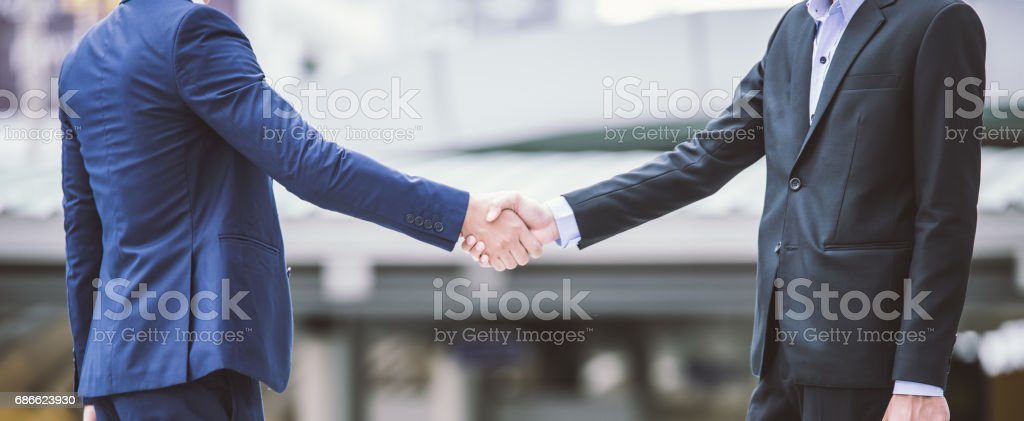 Business handshake concept. shaking hand of two businessman closing a deal city background 免版稅 stock photo