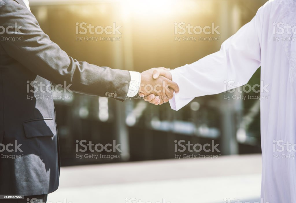Business handshake concept. shaking hand of two businessman closing a deal city background stock photo