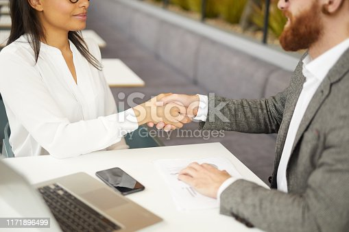 Close-up of young business people sitting at the table and shaking hands during business meeting in cafe