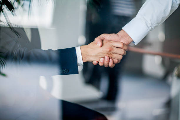 Business handshake in glass reflection in office stock photo