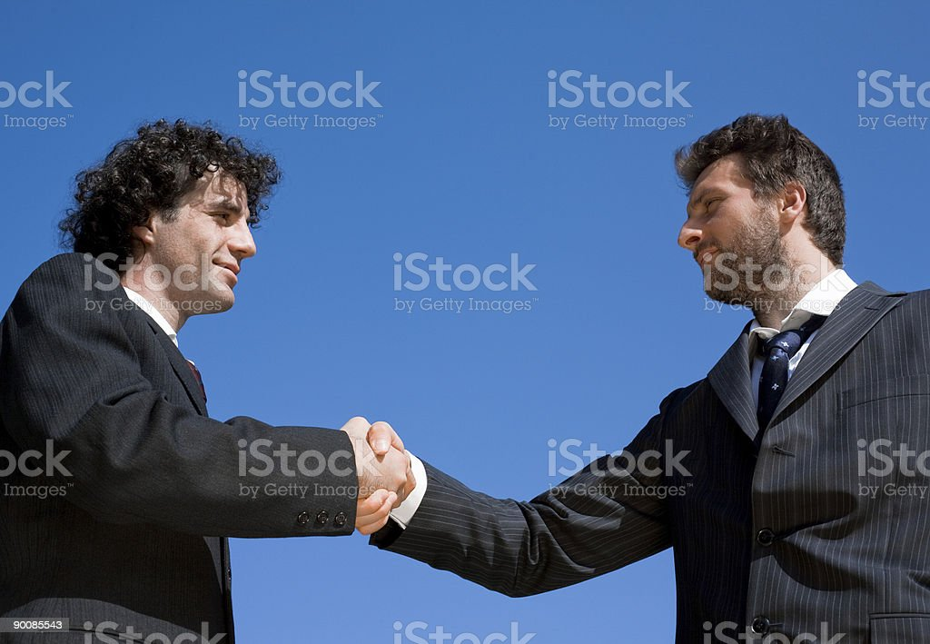 business handshake in the field with blue sky royalty-free stock photo