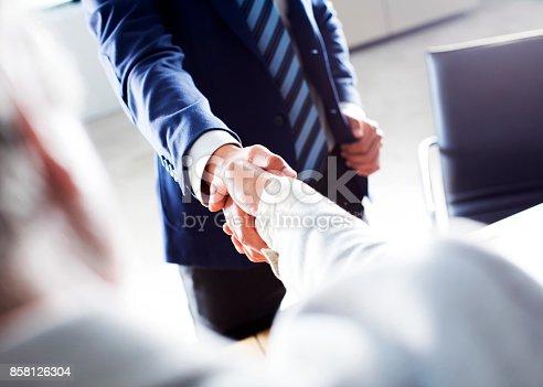 1008974324 istock photo Business handshake in the office 858126304