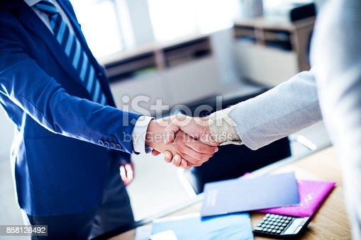 1008974324 istock photo Business handshake in the office 858126492