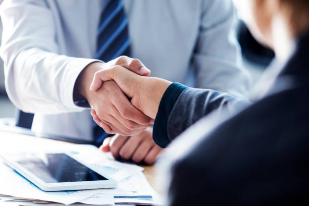 business handshake in the office - handshake stock pictures, royalty-free photos & images