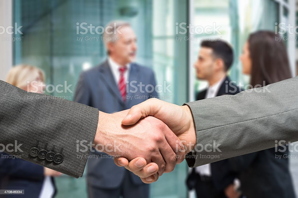 Business handshake. People talking in the background stock photo