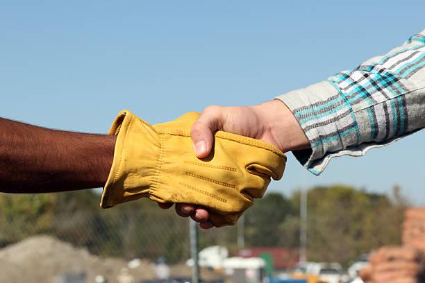 business handshake - arbeitshandschuhe stock-fotos und bilder