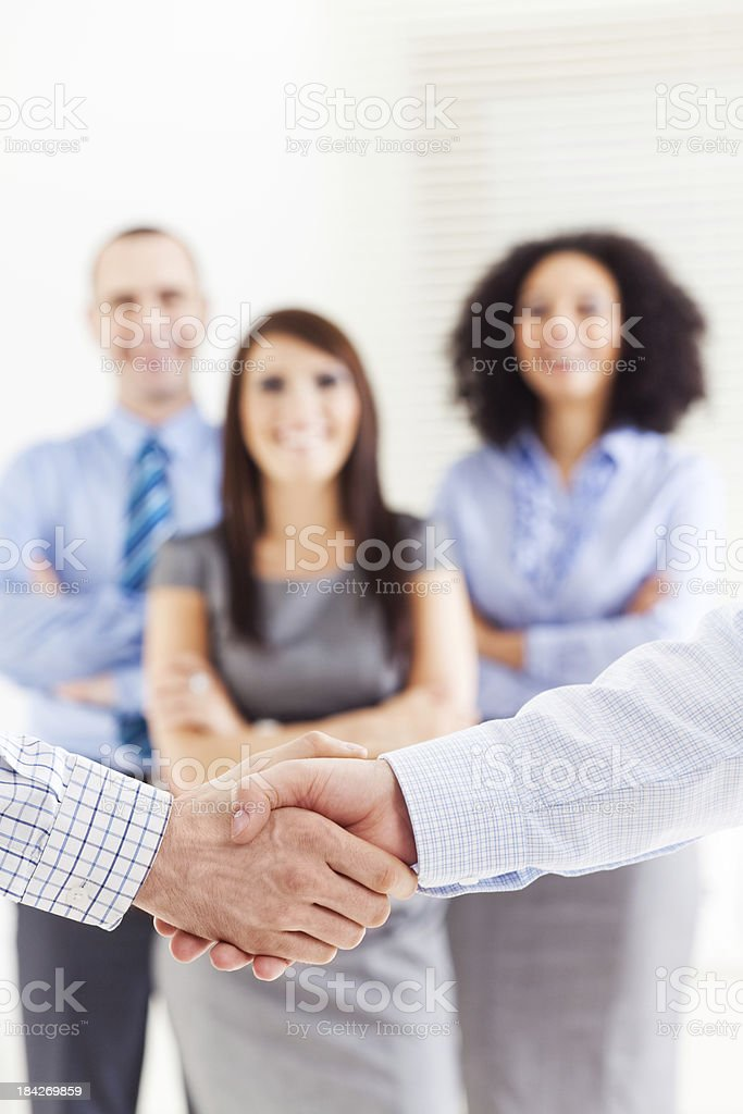 "Business handshake ""Close-up on the handshake between two businessmen. In the background people standing in a row, looking at camera and smiling."" Adult Stock Photo"
