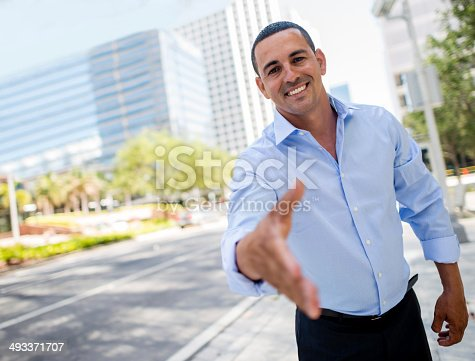 Business man with hand extended to handshake