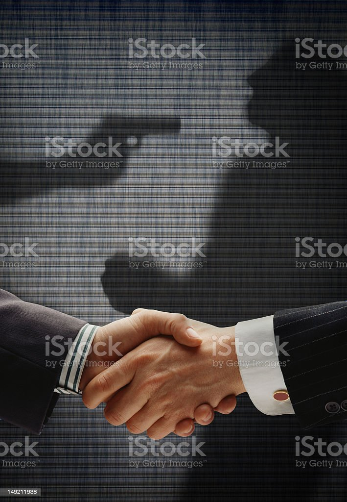 Business handshake with sinister shadow background stock photo