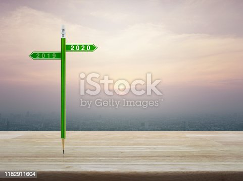 2020 and 2019 direction sign plate with green pencil on wooden table over modern office city tower and skyscraper, vintage style, Business happy new year planning concept