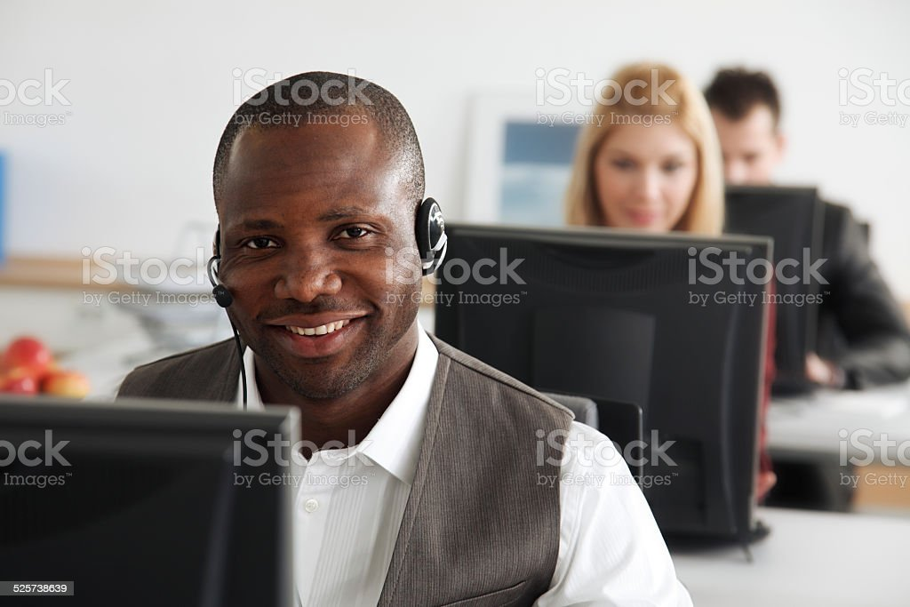 Smiling businessman with headset and people working behind him.