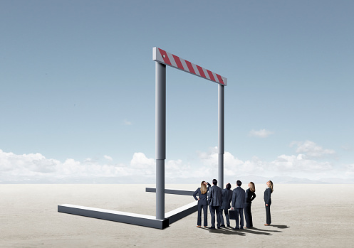 A group of business people look up at a giant hurdle that stands before them.